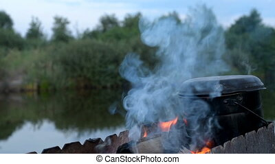 Preparing food on campfire in camping on pond background....