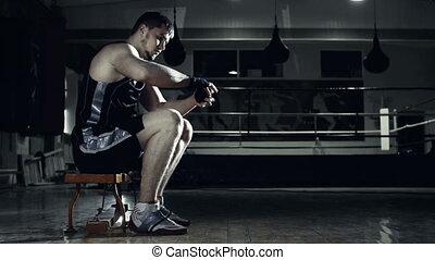 Preparing for Combat - Side view of boxer winding handwrap...