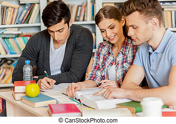 Preparing for exams in library. Three confident students reading a book together while sitting at the desk and against bookshelf in a library