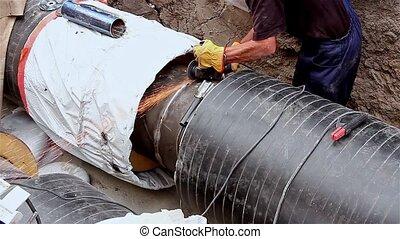 Preparing for next weld - Metal worker is grinding weld on ...