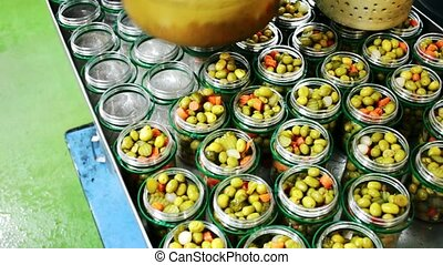 Filling glass jars with olives for pickling