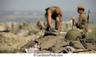 The soldiers are preparing for defense. Digging trenches and give ammunition.