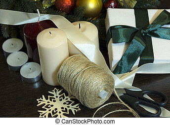 preparing for the holiday, Christmas, new year, a skein of thread, scissors, Christmas tree, red yellow balls, a box with gift tied with a green ribbon