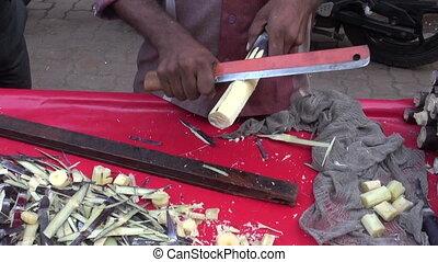 preparing fresh sugarcane pieces in Mumbai market, India