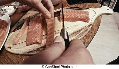 Preparing salmon for dinner - Cutting salmon on wooden...