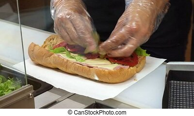 Preparing sandwich with ham and swiss cheese sandwich on brown bread