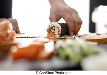 Preparing sushi - Sushi master preparing sushi in Japanese...