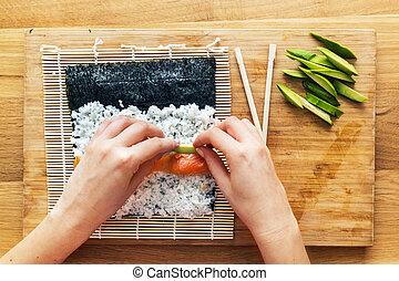 Preparing sushi. Salmon, avocado, rice and chopsticks on ...