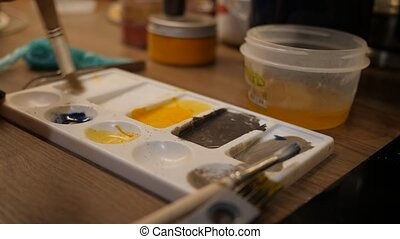 Preparing sweet food colors in white palette for painting on a cake