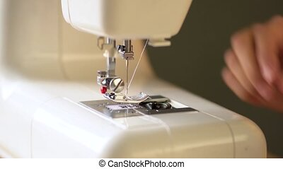 Preparing the sewing machine for work. Seamstress tucks thread into the eye of a needle. Installs the bobbin in the shuttle. Close up view.