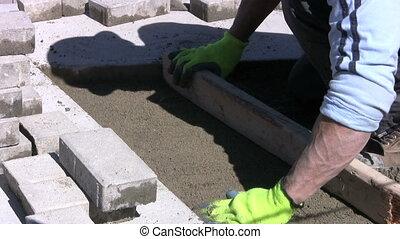 Preparing To Install Sidewalk Brick - A worker wearing green...