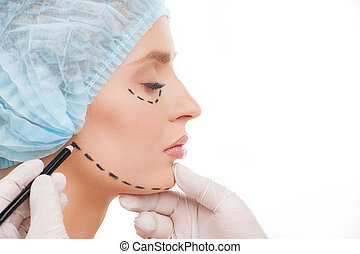 Preparing to plastic surgery. Side view of beautiful young woman in medical headwear and doctors hands marking her face with felt tip pen