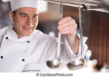 Preparing to work. Cheerful chef preparing cooking stuff ...