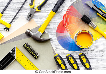 Preraring for home repair. Tools on grey wooden desk background top view