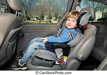 Preschool age boy in a booster seat - Boy in a booster seat...