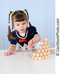 Preschool-age girl playing with wooden Lotto