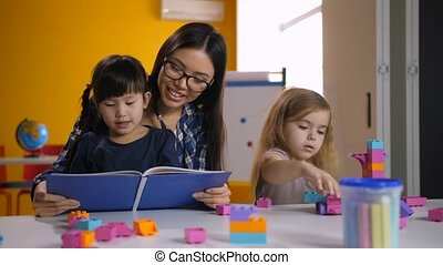 Preschool asian girl reading book with teacher