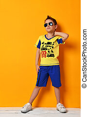 boy kid standing in blue tshirt with cars and shorts in sunglasses looking up on yellow background