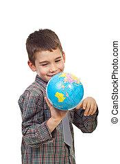 Preschool boy playing with a globe