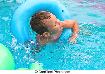 Preschool boy swims in pool on summer vacations