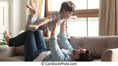Preschool child boy playing plane game flying in fathers ...
