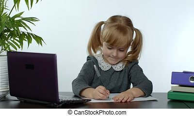 Preschool child girl distance online learning at home. Cute kid listening audio lesson studying at table using digital laptop computer, doing homework. Children remote education on covid-19 quarantine