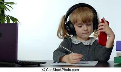Preschool child girl distance online learning at home. Cute kid listening audio lesson studying at table using digital mobile phone, doing homework. Children remote education on covid-19 quarantine