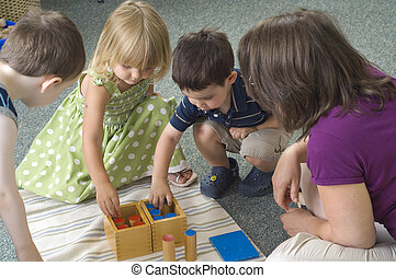 Children and teacher learn while playing with different shapes at the preschool class.