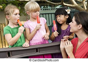 Preschool children on playground with teacher eating popsicles
