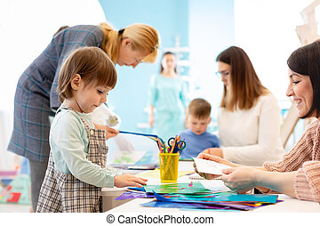 preschool children working with color paper, sciccors and glue on art class in kindergarten