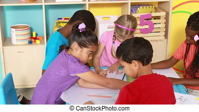 Preschool class drawing at table in classroom in playschool