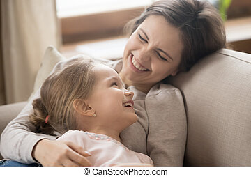 Preschool daughter and cheerful mother lying on couch joking laughing