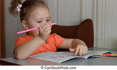 Preschool education. An amusing pretty girl sits at a table and draws in multicolored pencils. Child and creativity