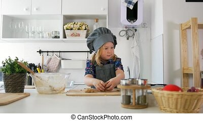 Preschool girl baker puts biscuits on a baking sheet, close...