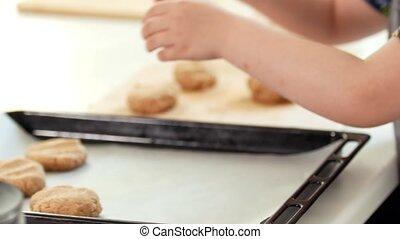 Preschool girl baker puts homemade cookies on a baking...