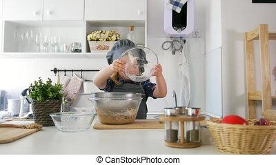 Preschool girl baker sifts flour in a bowl for cooking...