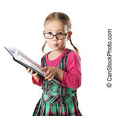 Cute preschool age girl wearing eyeglasses looking at a book