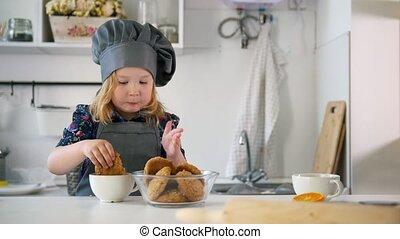 Preschool girl eats cookies prepared with her own hands