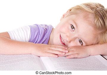 preschool girl laying on large book - Preschool girl laying...