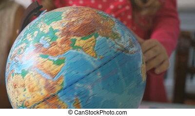 Preschool girl rotates the model of globe of world