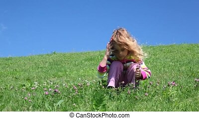 Preschool girl sits on meadow with grass