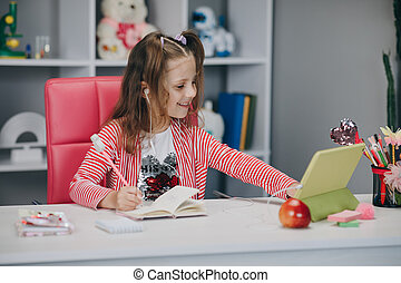 Preschool girl watching lesson online and studying from home. Kid girl taking notes while looking at computer screen following professor doing math on video call.