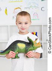 preschool kid playing with dinosaur