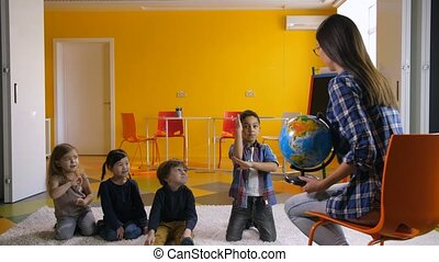 Preschool kids studying globe together with teacher