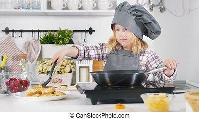 Preschool little girl baker making cheesecakes cookies on...