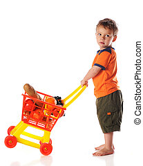 A preschool boy tipping a toy cartfull of groceries. Isolated on white.