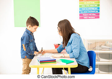 Preschool student getting her work graded - Profile view of...