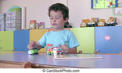 Preschool Student playing toy cars in the classroom