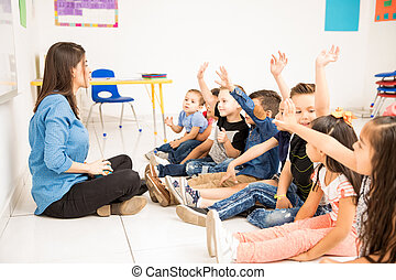 Preschool students raising their hands - Profile view of a...
