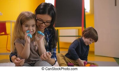 Preschool teacher and girl having fun with toys